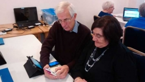 Colinton Club volunteer helping to sync a mobile phone and iPad